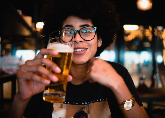 Portrait of young woman having beer in restaurant