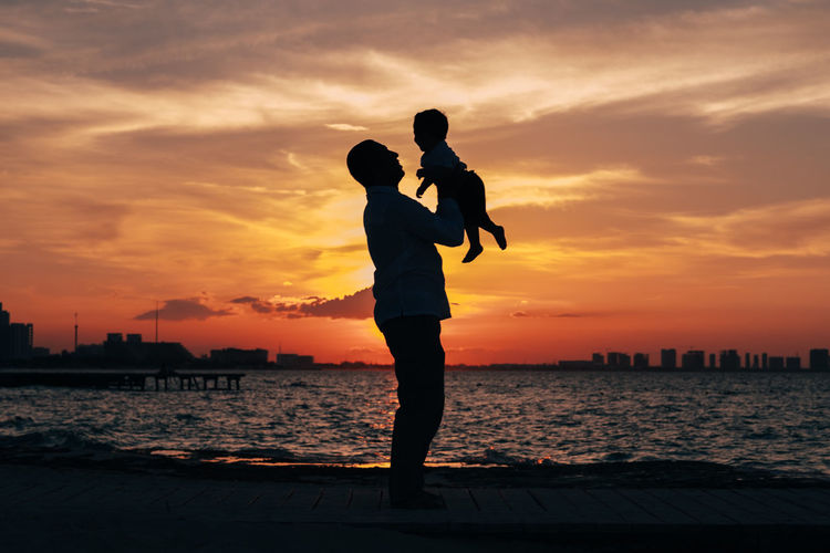 Silhouette Man Carrying Son While Standing By Sea Against Sky During Sunset