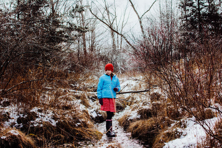 Tree Full Length Winter One Person Cold Temperature Plant Snow Nature Child Childhood Real People Day Bare Tree Lifestyles Walking Casual Clothing Land Warm Clothing Leisure Activity Outdoors Girl, Woman, Female One Person Standing Water Stream Winter Nature Discover Your City Red Hat Exploring