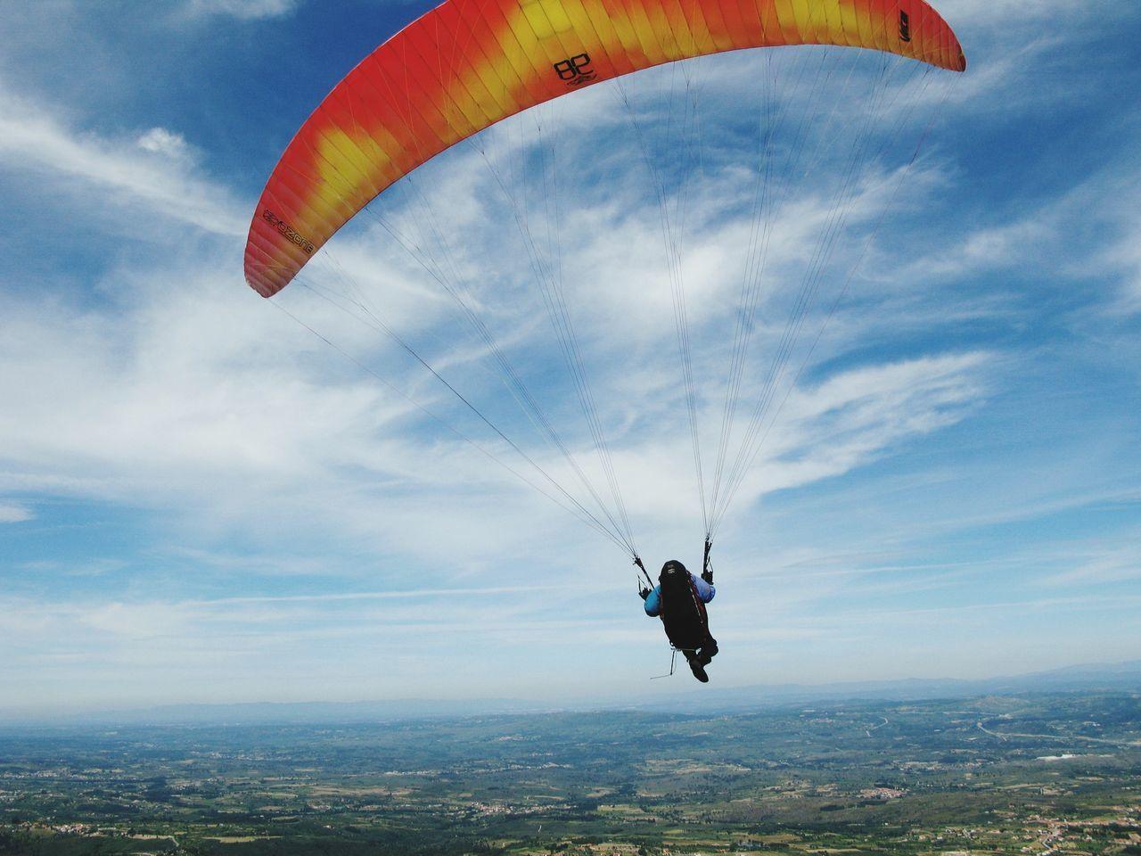 Person Paragliding Over Landscape