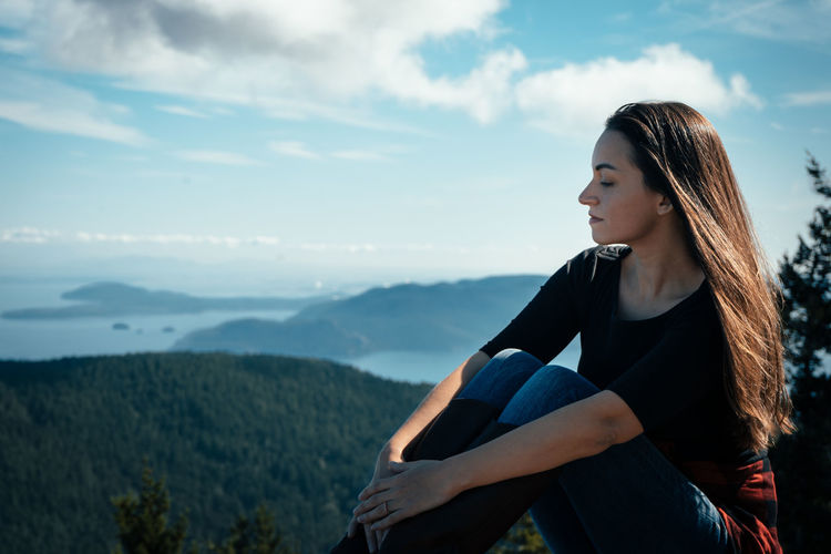 Woman sitting against blue sky