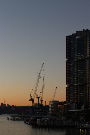 Commercial dock by buildings against clear sky during sunset