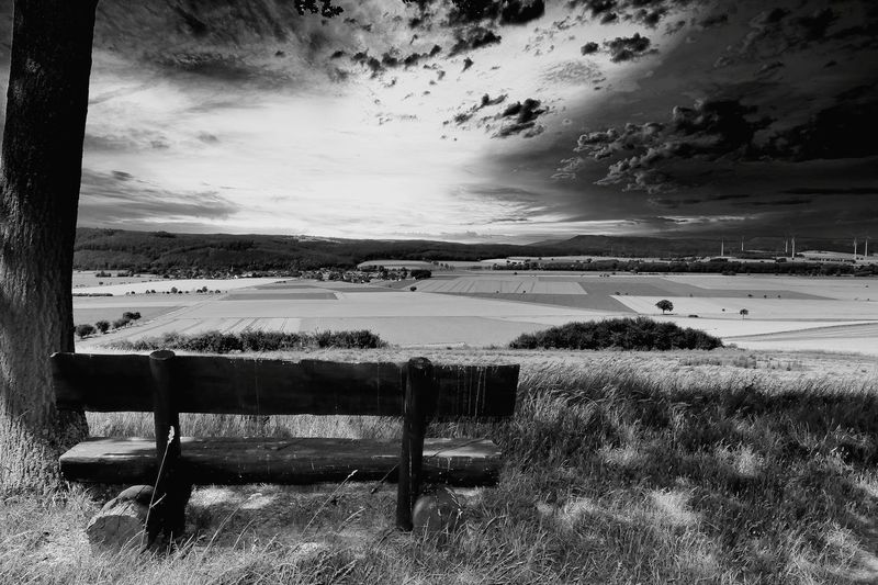 Empty bench on field against sky