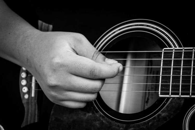 Close-up of man hand playing guitar