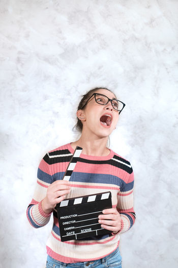Funny comedy face woman with movie clapper board Audition Eccentricity Film MOVIE Actress Cinema Clapper Board Comedy Entertainment Eyeglasses  Funny Face Grimace Indoors  Movie Slate Portrait Slapstick Slate Smirk Sneer Young Adult Young Woman