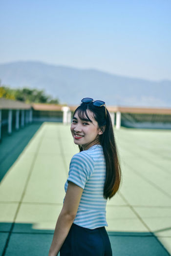 Portrait of cheerful young woman standing on building terrace against sky