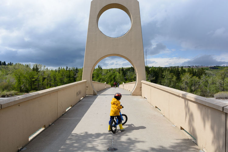 Rear view of man riding motorcycle on bridge against sky
