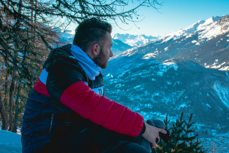 Side view of young man against snowcapped mountain