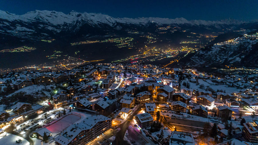 Architecture Beauty In Nature Building Exterior Built Structure City Cityscape Cold Temperature Community High Angle View House Illuminated Landscape Mountain Mountain Range Nature Night No People Outdoors Residential Building Scenics Sky Snow Town Tree Winter