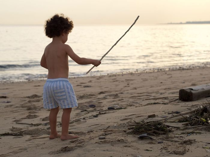 Shirtless boy holding stick while standing at beach