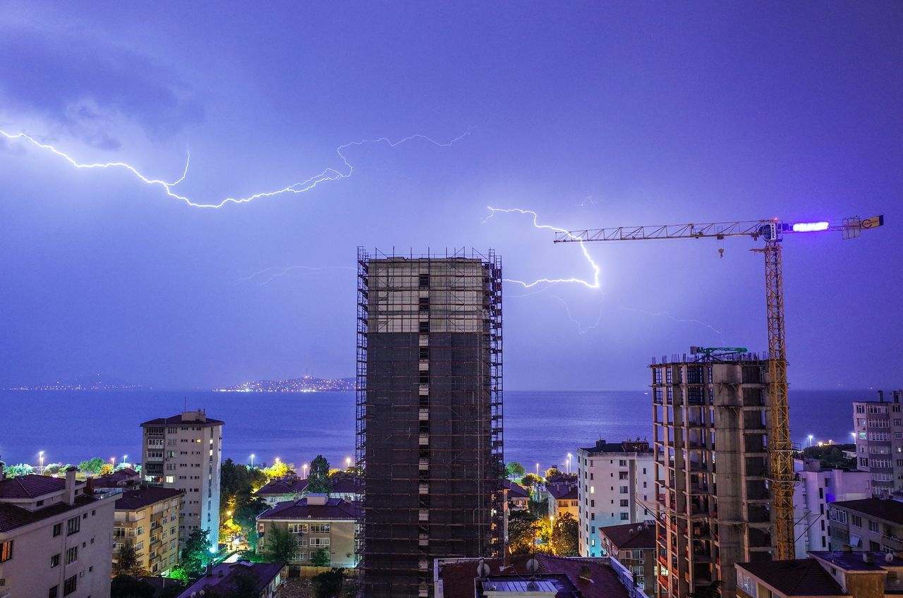 Lightning above sea and buildings in city