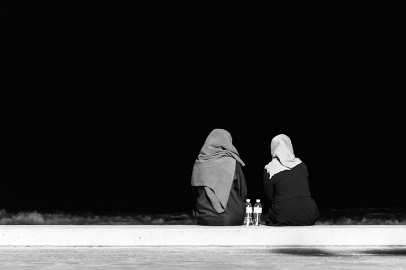 Rear View Of Female Friends On Beach Against Clear Sky At Night