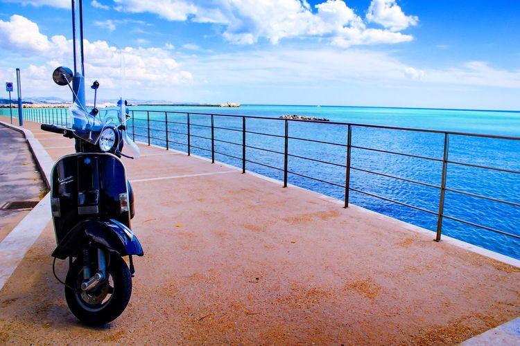 Bicycle on railing against sea