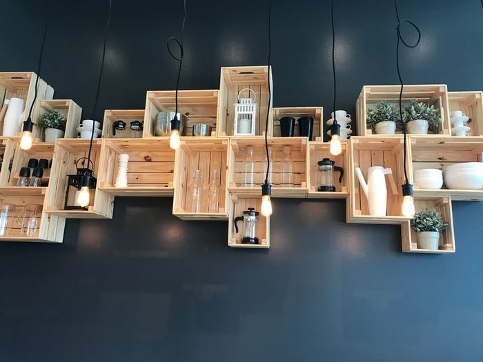 Low angle view of various objects arranged in shelves mounted on wall