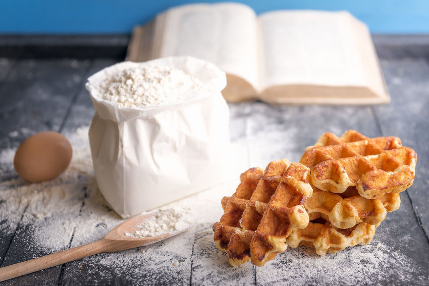 Cooking theme image with a bunch of delicious Belgian waffles, egg, a bag of flour and an open cookbook, on a rustic wooden table. Baked Bakery Baking Belgian Waffles Confectionery Cooking Book Food Food And Drink Pastry Recipe Rustic Table Table