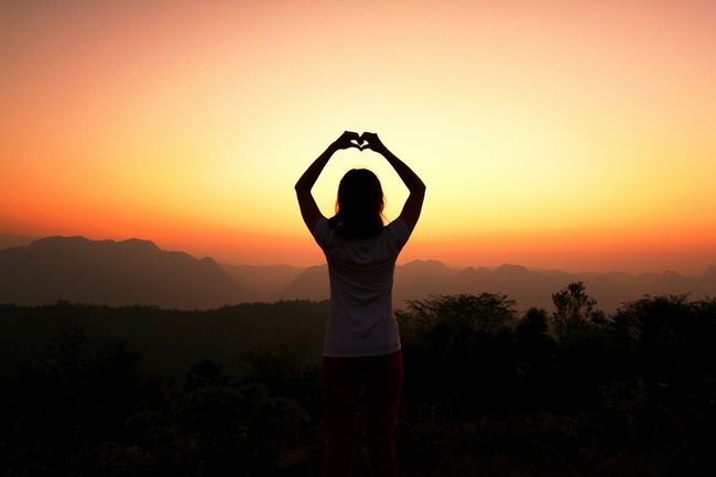 Silhouette of women make heart sign with her hand and finger at sunset time. Lovly and Valentine day concept. Mountain View National Park Valentine's Day  Arms Raised Beauty In Nature Dawn Of A New Day Heart Landscape Lifestyles Lovely Nature One Person Orange Color Real People Scenics Silhouette Sky Standing Sunrise Sunset Tranquility Tree Twilight Sky Yoga EyeEmNewHere