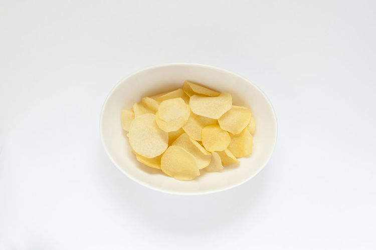 Who doesn't love a snack? Top view shot of a bowl with crispy potato chips. Abstract Bowl Chips Close-up Crispy Day Delicious Food Food And Drink Freshness Golden Healthy Eating Indoors  Isolated Junk Junk Food No People Potato SLICE Snack Studio Shot Tasty Thin White Background Yellow