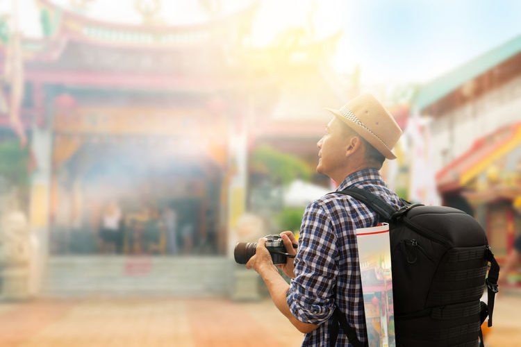 Man holding camera while standing in front of temple
