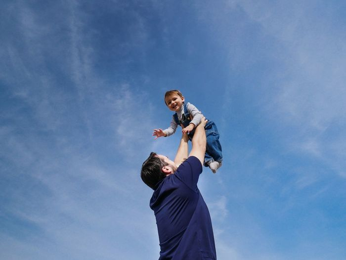 Low angle view of father playing with son against sky