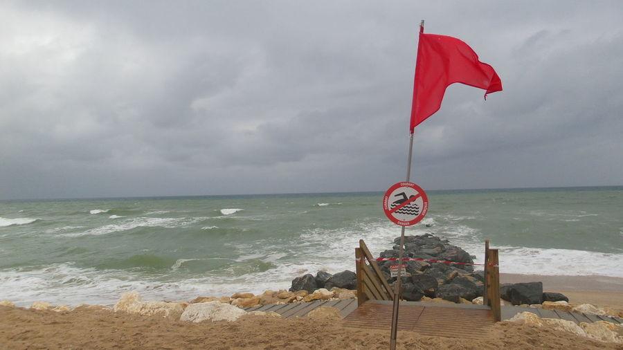 Red flag on calm beach against the sky