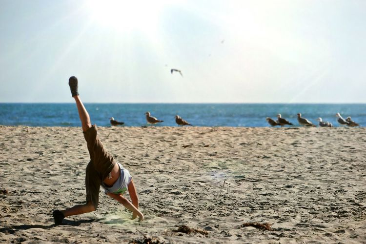 Boy doing cartwheel on beach against sky