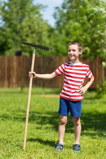 Full length of boy standing on grass against plants