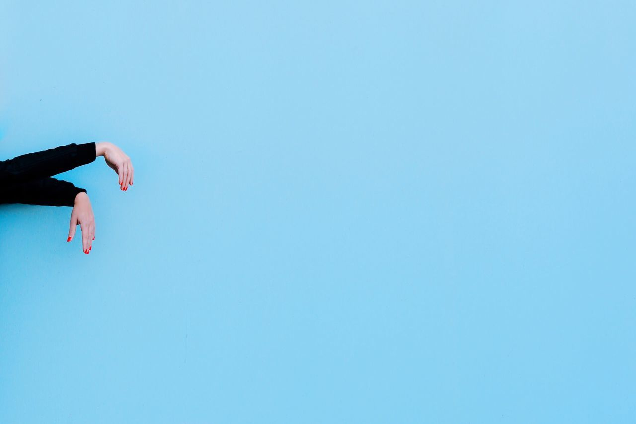 Cropped hands of woman by blue wall
