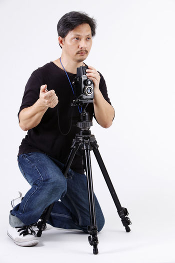 studio shot of photographer capturing images Photographer Camera Old Hobbies Human Face Human Hand People Photography Phtographing Antique Medium Format Camera Holding Capturing Capturing An Image Tripod Cable Cable Release White Background Studio Shot Man Males  One Person Indoors  Full Length Cut Out Front View Mid Adult Casual Clothing Technology Photography Themes