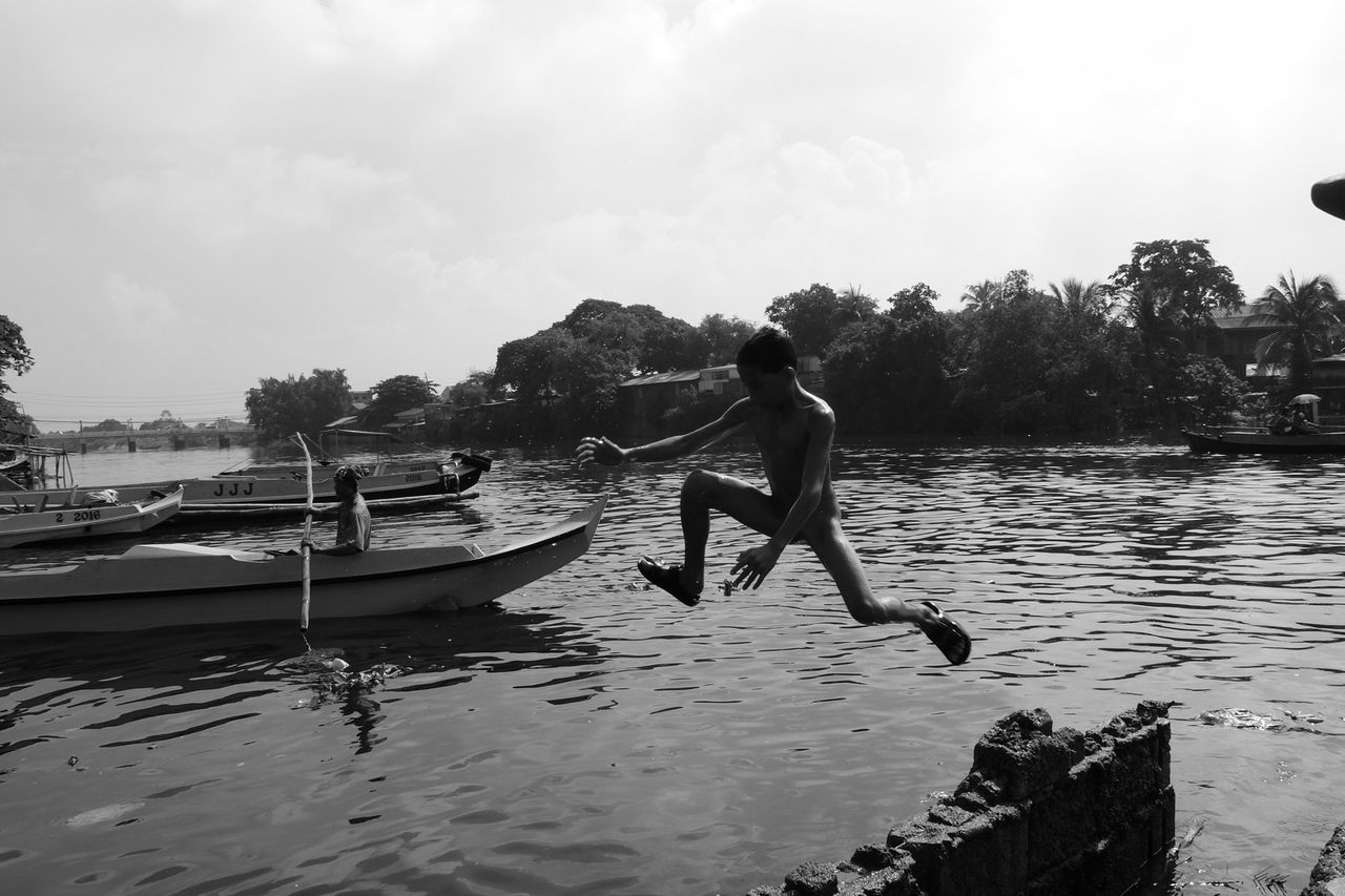 water, outdoors, one person, real people, mid-air, day, jumping, nature, full length, sky, nautical vessel, shirtless, tree, men, swimming, one man only, young adult, people