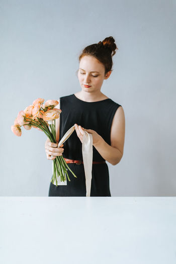 Woman Tying Flowers With Ribbon At Table Against Wall