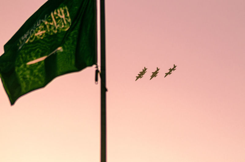 Low angle view of airplanes in sky with flag