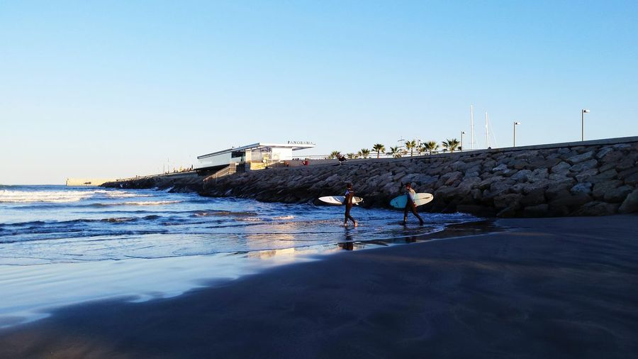 Side View Of Man And Woman With Surfboards Walking At Beach