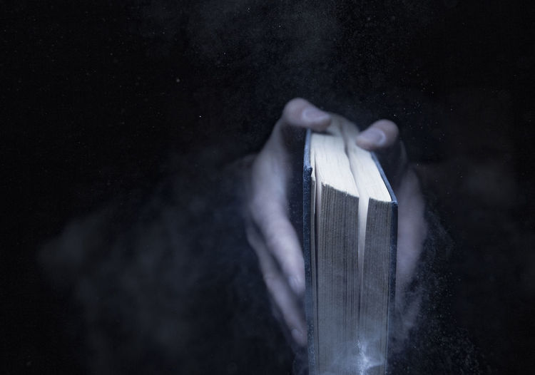 Close-up of hands holding book against blurred background