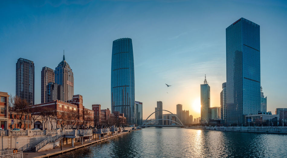 View Of Skyscrapers By River Against Buildings In City