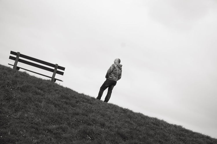 A single person standing next to a single empty wooden bench on the horizon above a grass field against a large grey clouded sky depicting loneliness, thinking, pondering, grieve, being alone, sadness One Person Real People Full Length Leisure Activity Nature Rear View Sky Land Lifestyles Day Field Walking Standing Grass Plant Adult Men Landscape Women Outdoors Warm Clothing