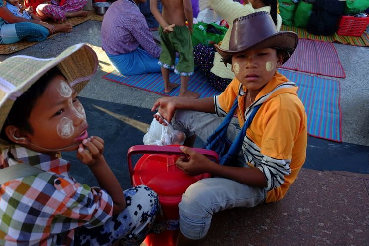 Two local boys selling goods, fascinated by me at Mount Kyaiktiyo (Golden Rock) Pagoda Buddhism Buddhist Culture Composition Full Frame Golden Rock Golden Rock Pagoda Hats High Angle View Kinpun Looking At Camera Making A Living Mount Kyaiktiyo Mount Kyaiktiyo Pagoda Myanmar Outdoor Photography Place Of Pilgrimage Place Of Prayer Place Of Work Place Of Worship Portrait Of Boys Selling Sitting Thoughtful Togetherness Two Boys