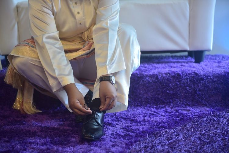 Low Section Of Bridegroom Tying Shoelace On Purple Rug During Wedding Ceremony