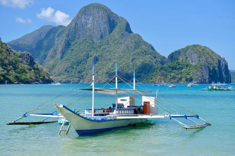 Outrigger Boat Sailboat Turquoise Colored Non-urban Scene Waterfront Mountain Range Mountain Sea Water Nature Outdoors Tranquility Outrigger Canoe Transportation Low Tide Canoe Beauty In Nature Philippine Islands No People Ebb Bangka Outrigger Moored El Nido, Palawan Tranquil Scene El Nido Islands Nautical Vessel Mode Of Transportation Philippine Beaches Palawan Island Scenics - Nature Bacuit Archipel Idyllic Yacht It's More Fun In The Philippines Wooden Boat Island View  Island Tour Boat Trip Filipino Culture Island Vacation