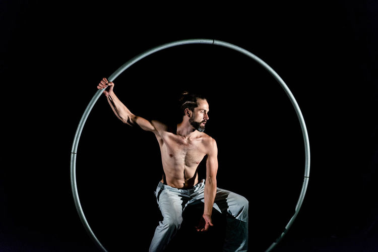 Circus Adult Black Background Circle Front View Geometric Shape Holding Lifestyles Men Muscular Build One Person Plastic Hoop Shape Shirtless Skill  Sport Standing Strength Studio Shot Three Quarter Length Young Adult Young Men
