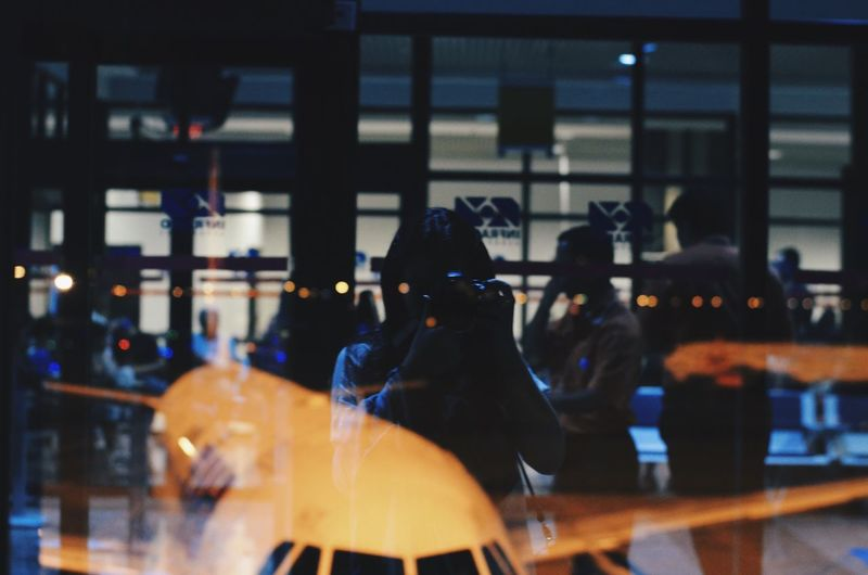 Woman photographing airplane with reflection on window glass at airport
