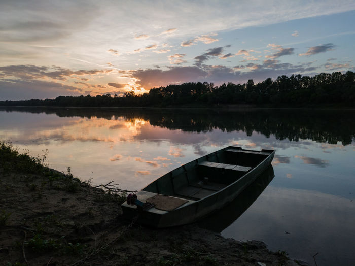 Boat moored in lake against sky during sunset