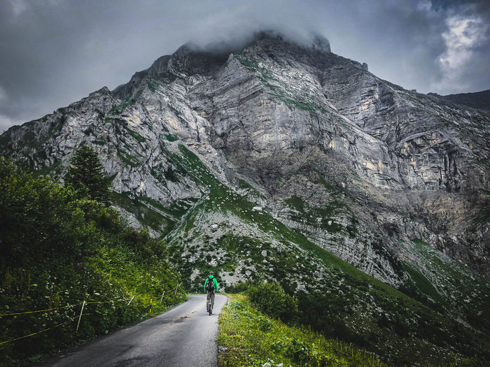 Rear view of man riding bicycle on road against mountains