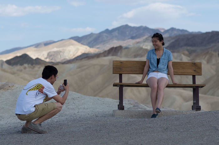 """Smile!"" Bench California Canyon Coulors Dantesview Day Death Valley Death Valley National Park Desert Friendship Holidays Landscape Mountain View Mountains Outdoors Perspective Real People Rock Formations Sitting Taking Photos The Tourist Traveling USA Woman Young Lost In The Landscape Connected By Travel"