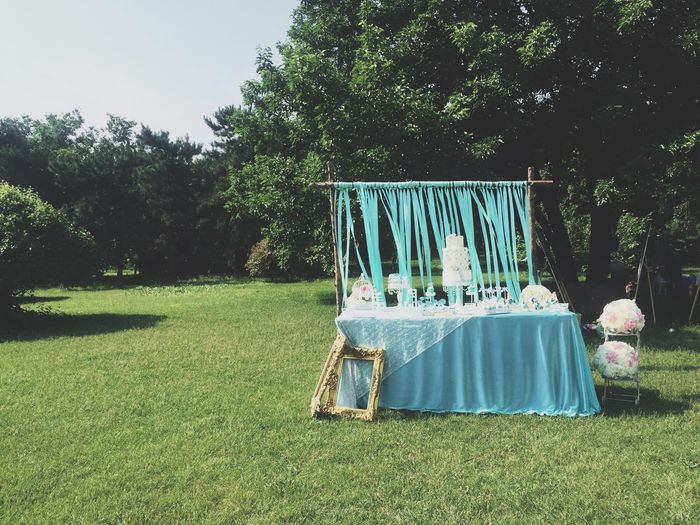 Wedding cake on table against trees in lawn