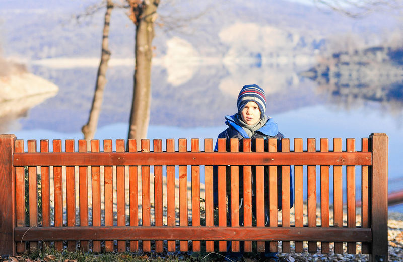 A boy standing behind the railing. Autumn Colors Behind The Railing Boy Portrait Childhood Memories EyeEmNewHere Flashback Headwear Kid Photography Kidsphotography Lakeview Mountain And Lake Nice Composition Protection Railing Safety Unreachable Warm Clothing Wooden Railing The Portraitist - 2017 EyeEm Awards
