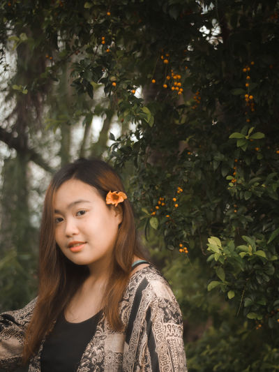Portrait of a beautiful young woman standing against plants