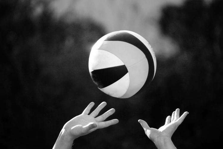 Midsection of person playing with ball against blurred background