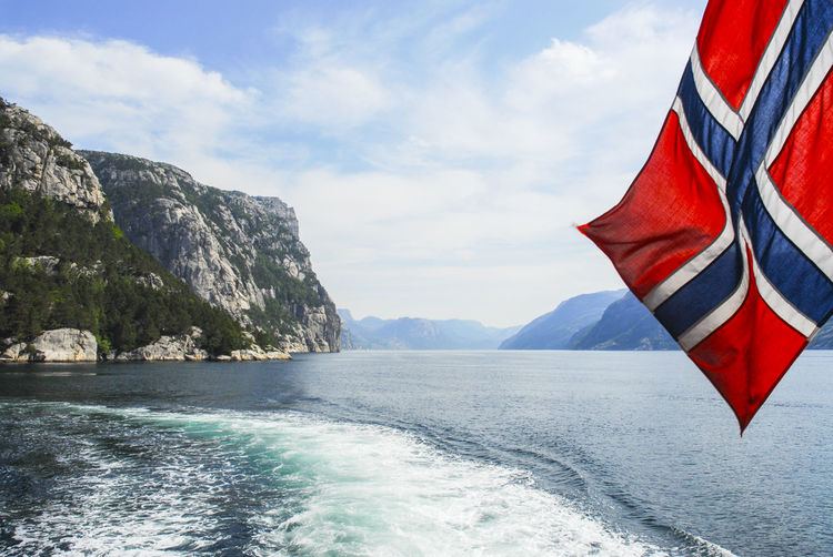Norwegian flag over sea against mountains