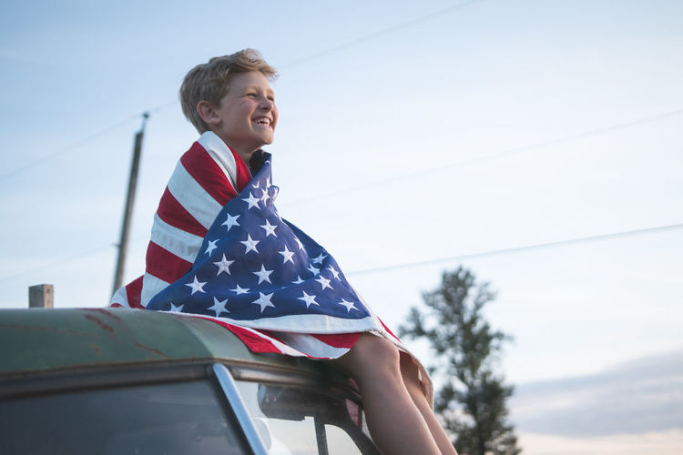 Happy boy with american flag sitting on vehicle against sky during sunset