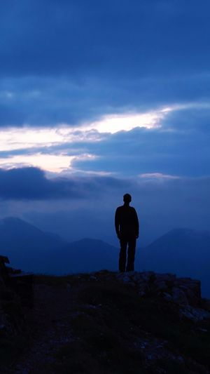 Silhouette Man Standing On Cliff Against Cloudy Sky